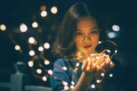 woman in blue shirt holding lighted string of lights